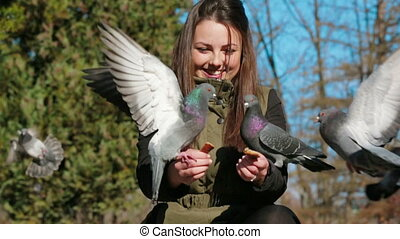 Cheerful Girl Feeding Pigeons In Park