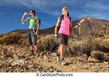 Hiking. Young couple hiking / backpacking in very scenic and...