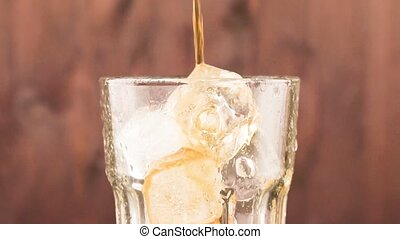 pouring fresh coke with ice cubes isolated on wood background, summer time