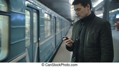 Man typing sms standing on the subway platform - Young man...
