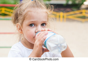 Three year old girl drinks from a bottle