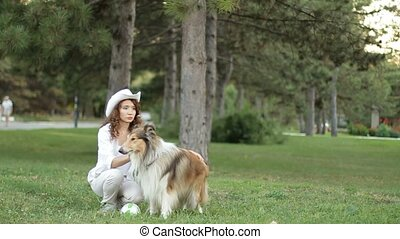 Girl with her dog in the park collie. dog training. - Girl...