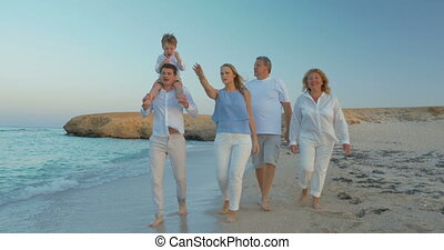 Big Family Walking by the Sea - Steadicam shot of members of...