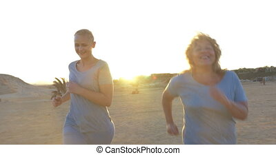 Mother and Daughter Jogging - Steadicam shot of young and...