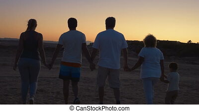 Family on vacation walking holding hands - Steadicam back...