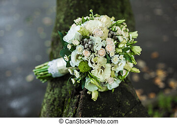 Very beautiful bridal bouquet lying on the tree
