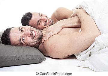 A homosexual couple onder a bed in studio white on studio.