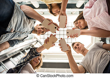 Students with gadgets - Group of students standing in circle...
