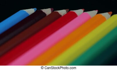 Colored Pencils Twelve Pieces Lie on a Black Table. Smooth...