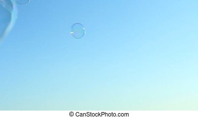 Big bubble flying over blue sky.
