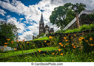 Orange lillies and St Peters Roman Catholic Church, in...