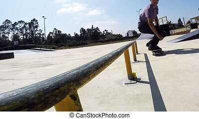 Skateboarder grinding down rail
