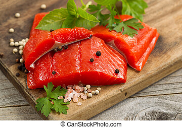 Fresh bright red Copper River Salmon fillets on rustic...