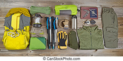 Hiking and camping gear organized on rustic wooden boards -...