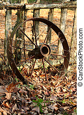 Old wagon wheel leaning on a fence