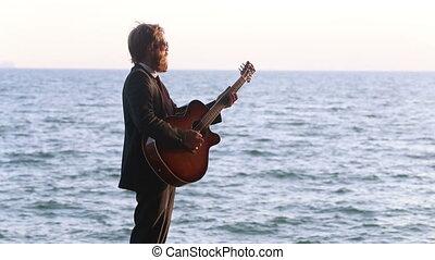 guitarist in black suit plays against sea