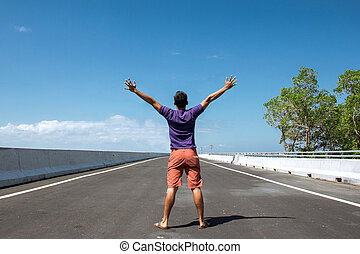 Man standing in the empty highway with both arms open, his back against the camera,  clear sky background