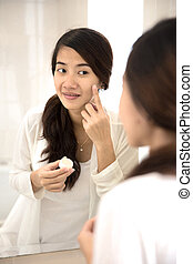 Happy asian woman putting make-up on, smiling at mirror - A...