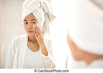 Young Asian woman taking care of her face - A portrait of an...
