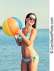smiling teen girl in sunglasses with ball on beach - sea,...