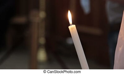Woman holding candle in church, HD