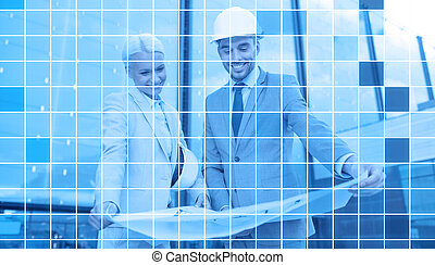 smiling business people in helmets with blueprint -...