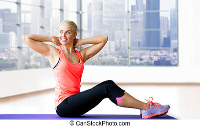 smiling woman doing sit-up on mat over gym - fitness, sport,...