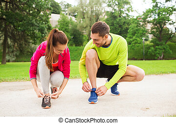 smiling couple tying shoelaces outdoors - fitness, sport,...
