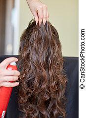 stylist with hair spray ma
