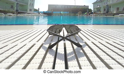 Sunglasses at poolside of hotel swimming pool outdoor...