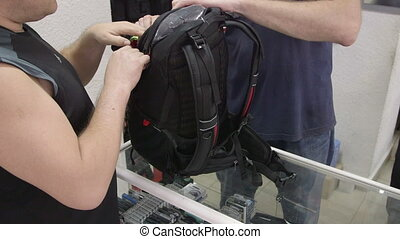 Customer looking for new camera backpack at photographic...