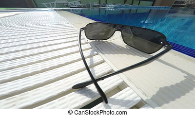 Sunglasses at the edge of hotel swimming pool outdoor