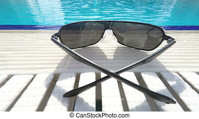 Sunglasses at poolside of hotel swimming pool outdoor