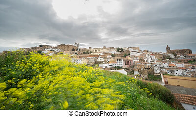 Time Lapse of Caceres, cloudy sky, yellow flowers in the foreground, 4K
