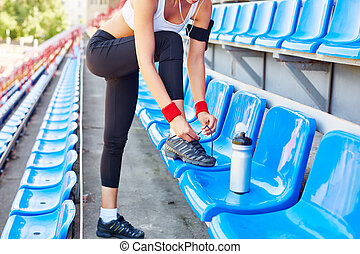 Tying shoelaces - Modern girl with iphone tying shoelaces on...