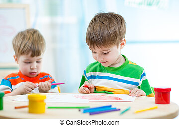smiling children draw and paint at home or day care center