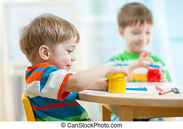 children play and paint at home or kindergarten or...