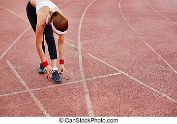 Tying shoelace at stadium - Fit girl in activewear tying her...