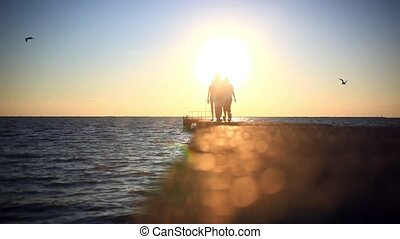 Silhouettes of people going to the sun on The pier at sunset...