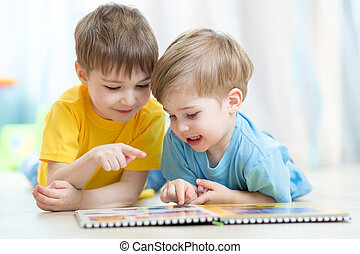 Kids brothers practice reading together looking at book...