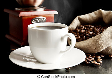 Cup of coffee with mill,bag full of coffee beans on black