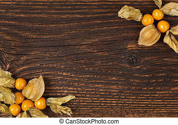 Physalis background with copyspace. Ground cherry on wooden...