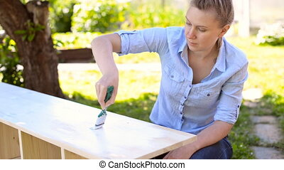 Painting wooden furniture - Woman with brush painting wooden...