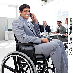 Businessman in a wheelchair on phone during a meeting with...
