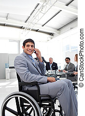 Smiling businessman on phone sitting in a wheelchair at a...