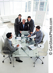 Business people working at a computer in a meeting smiling...