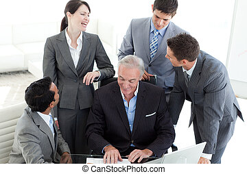Laughing business team looking at a document with their...