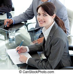 Smiling businesswoman studying a document in a meeting with...
