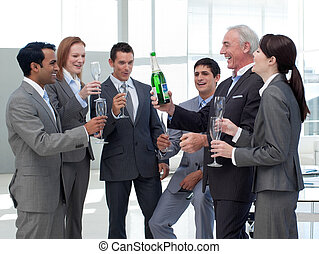 Smiling business people celebrating a success with Champagne