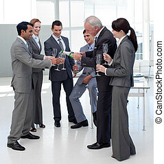 Cheerful manager serving Champagne to his team